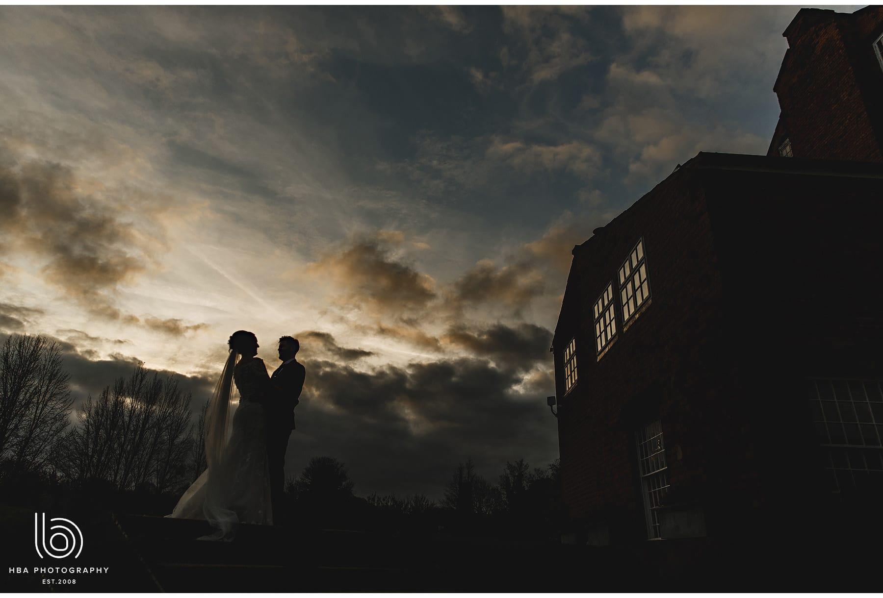 the bride & groom as the sun sets