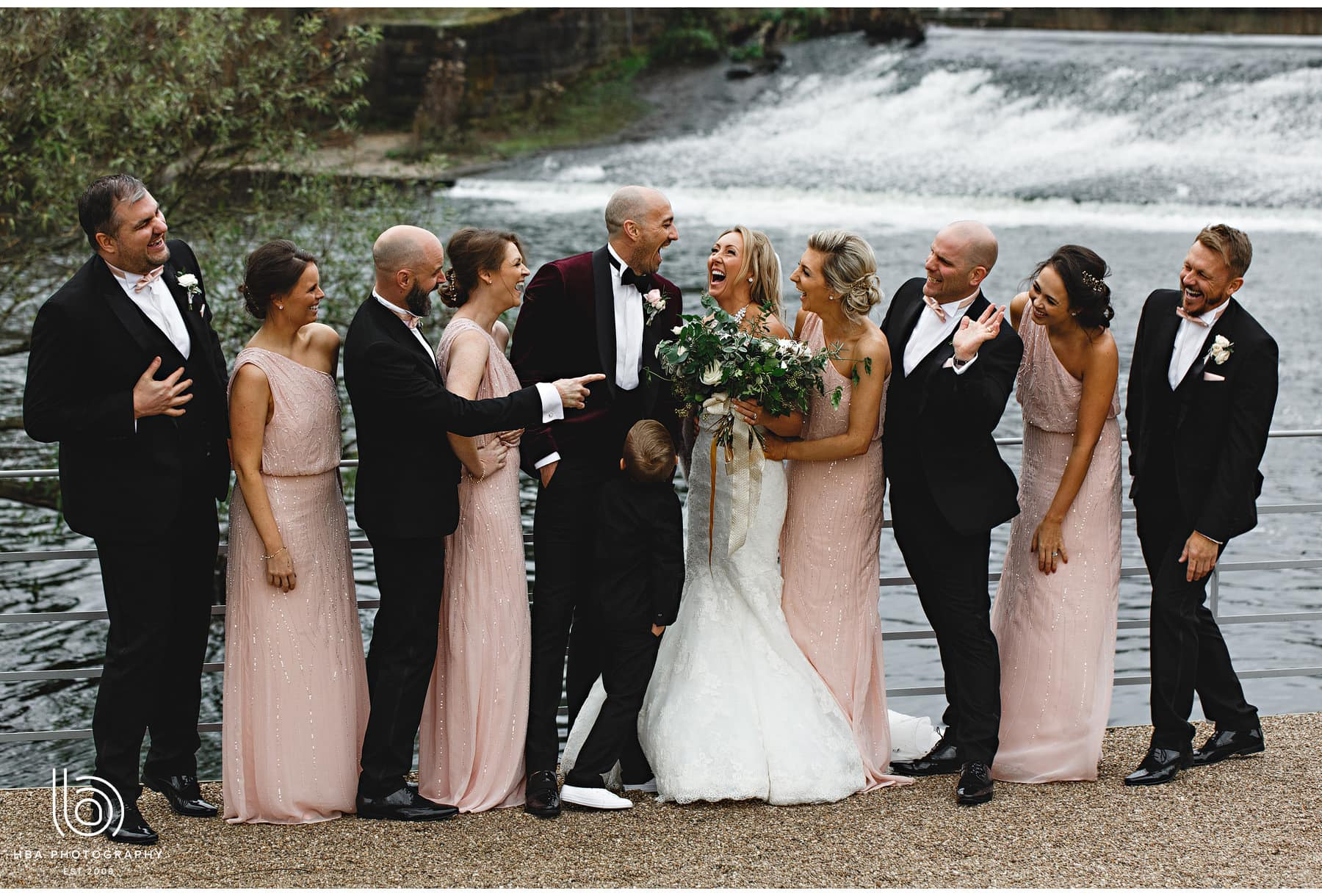 the bride & groom with their wedding party by the river