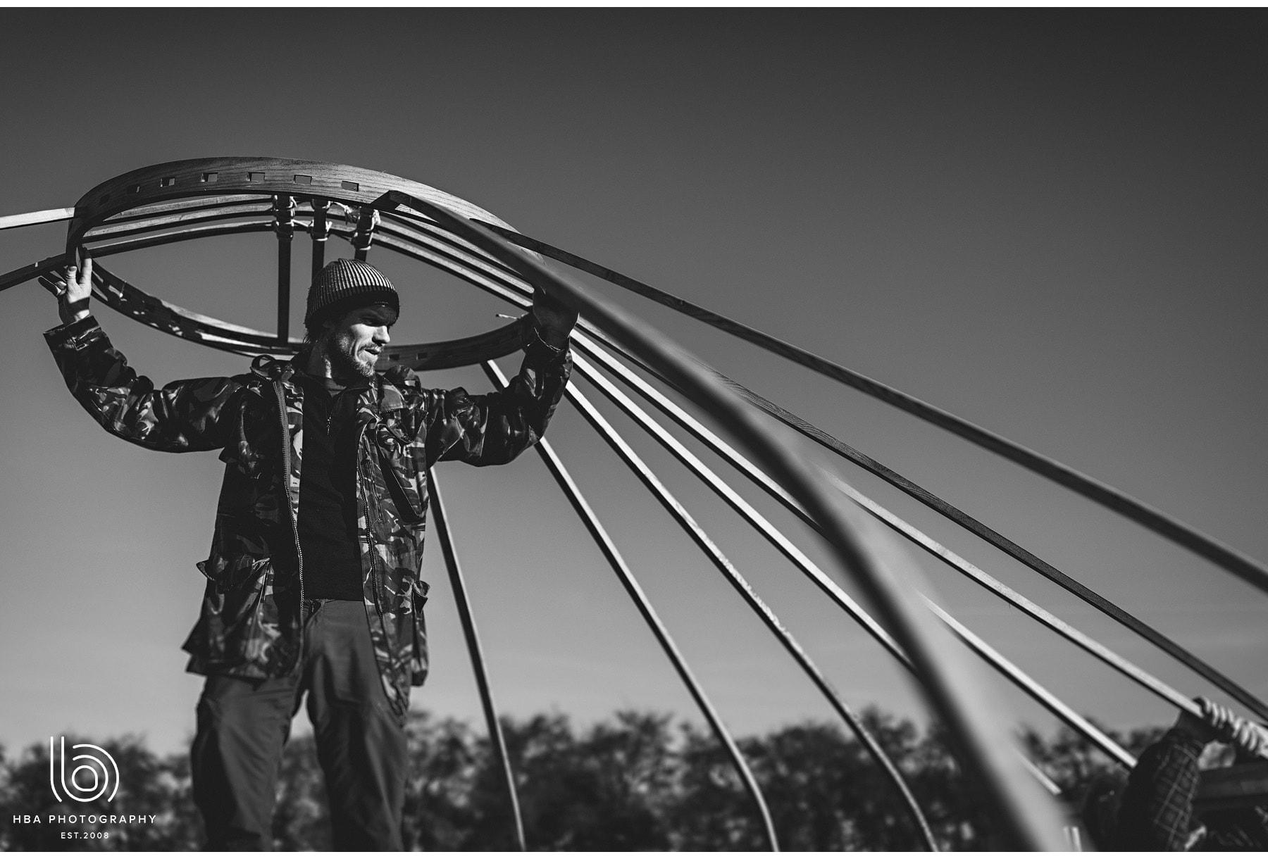 black and white of man putitng up yurt for wedding