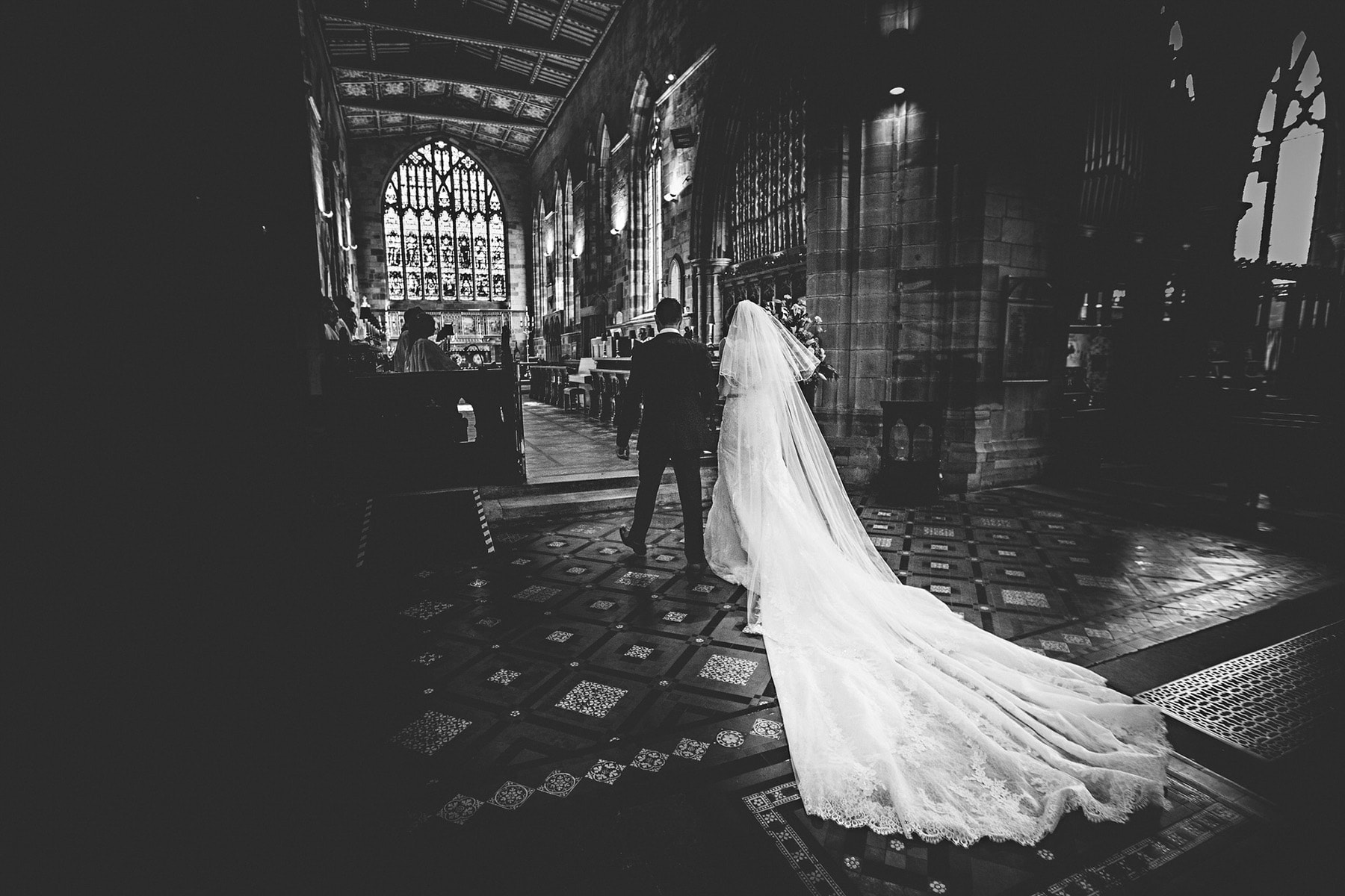 the bride ands groom in black and white walking up the aisle at St Oswalds Church in Ashbourne