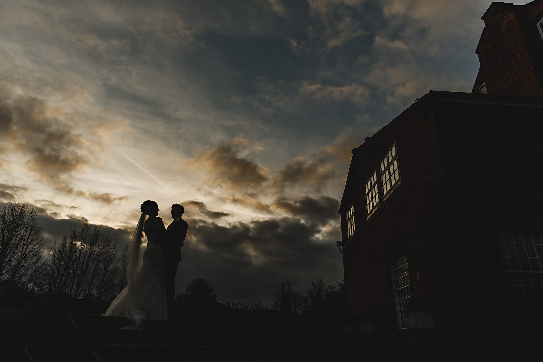 the bride and groom stood in the evening light at the west mill in derbyshire