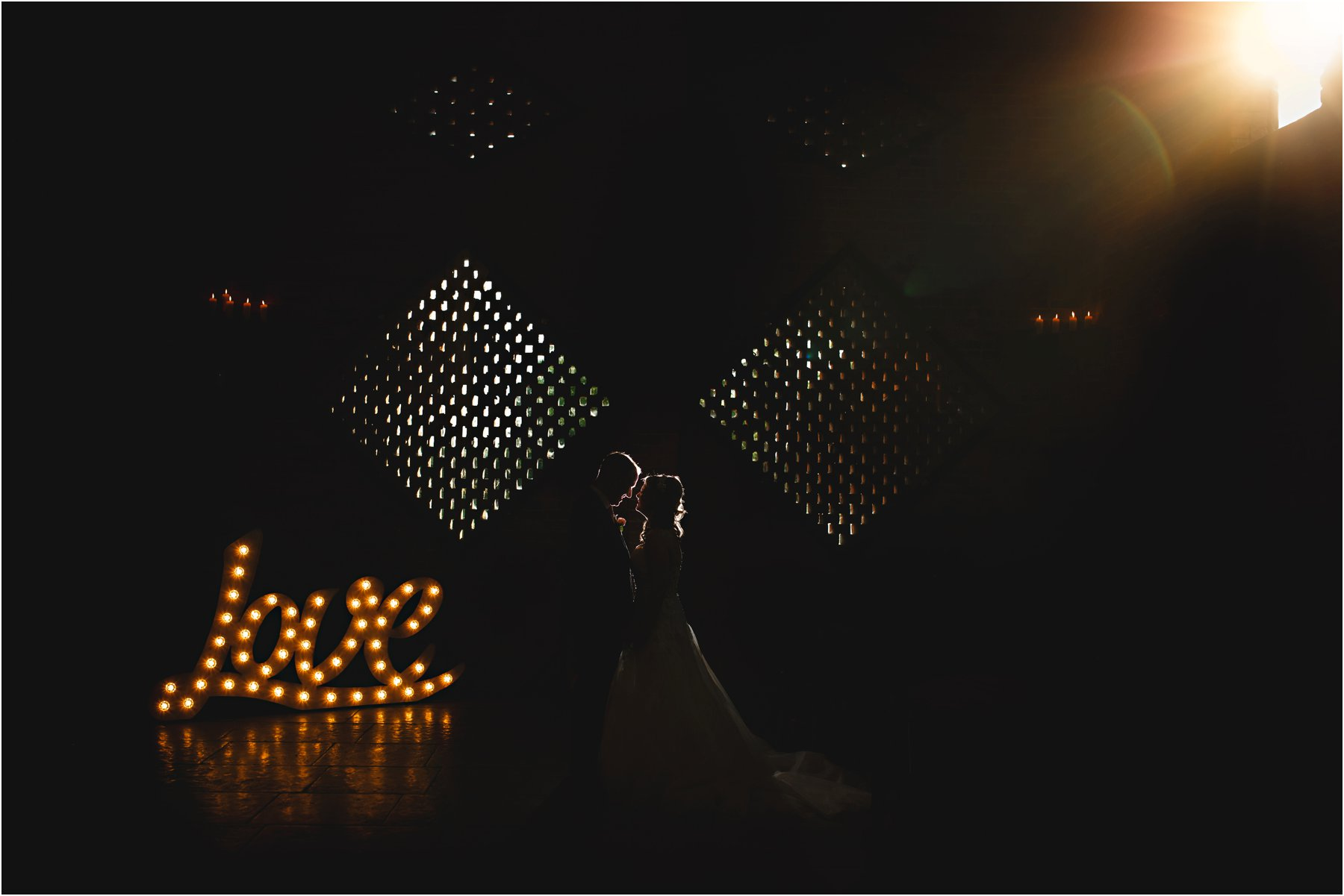 the bride and groom dancing with LOVE letters