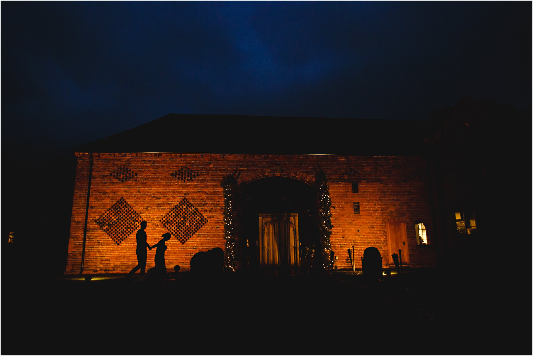 The bride & groom walking in silhouette at Shustoke Farm barn