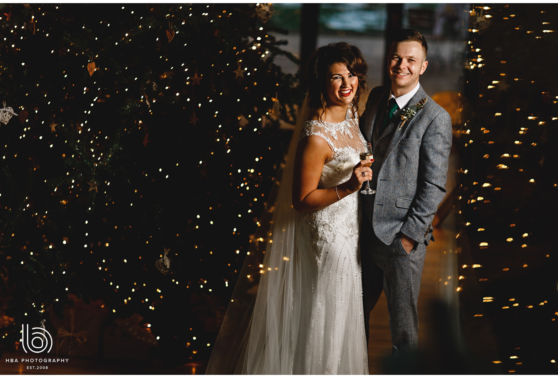 the bride & groom laughing by the christmas tree