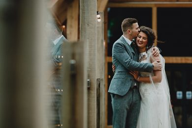 The bride and groom hugging together outside the mill barns in Shropshire