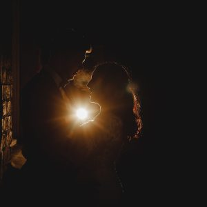 the bride and groom stood in darkness with an orange light at the west mill in Derbyshire