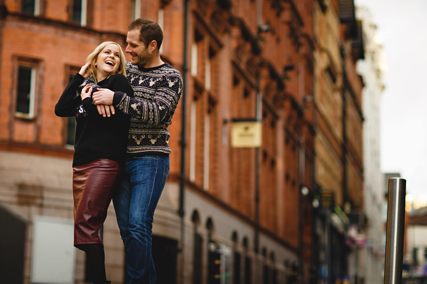 couple hugging and laughing against red brick buildings in the city