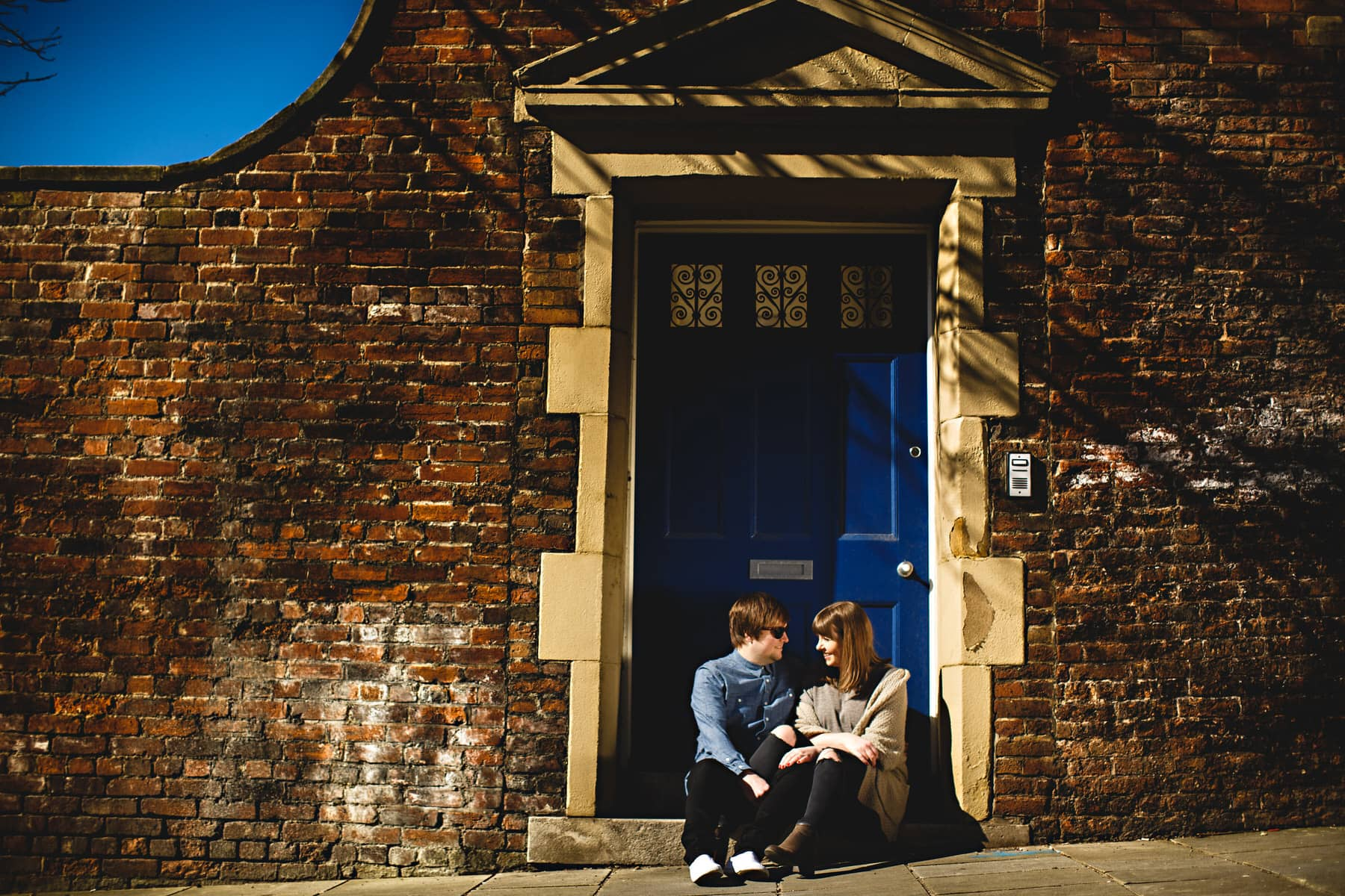 a couple sat on the door step in front of a blue door