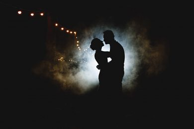 The bride and groom in smoke at Shustoke Barns in Warwickshire