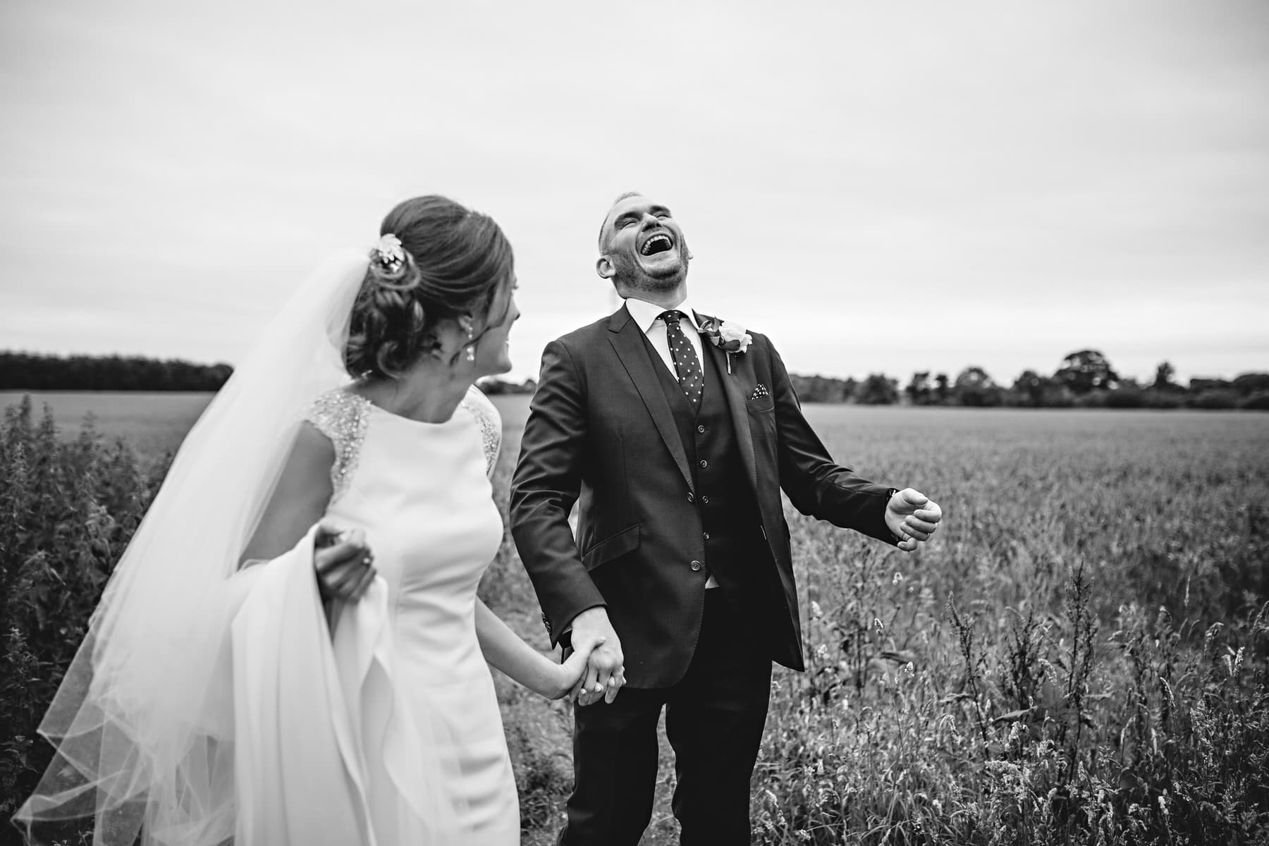 black and white wedding photo laughing at Shustoke Barns in Warwickshire