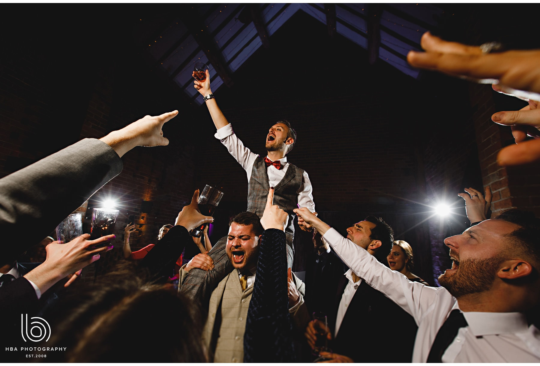 the groom lifted onto friends shoulders