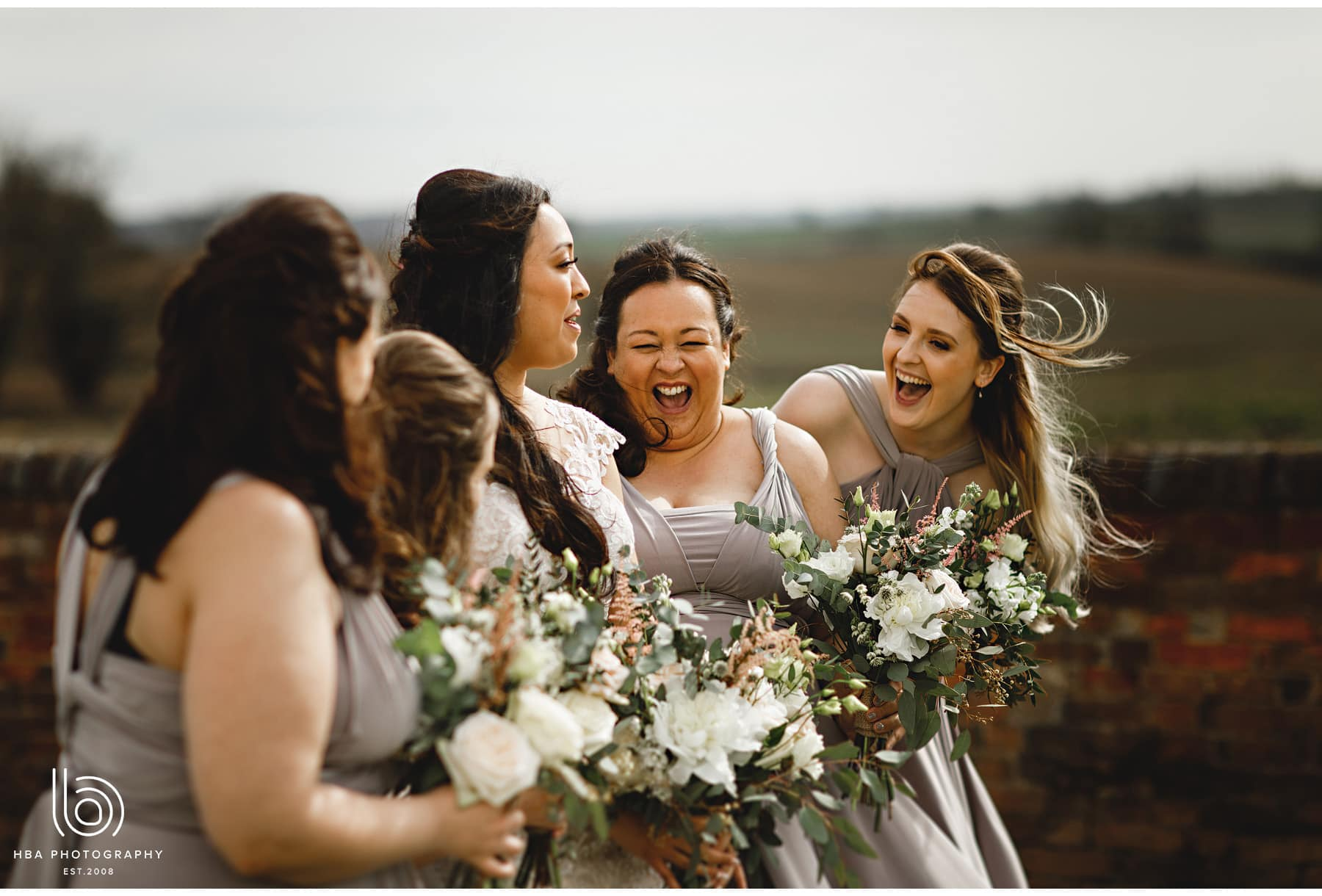 the bride and bridesmaids laughing