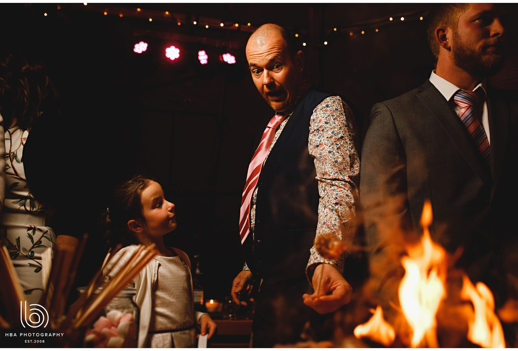 wedding guests roating marshmallows in the tipi