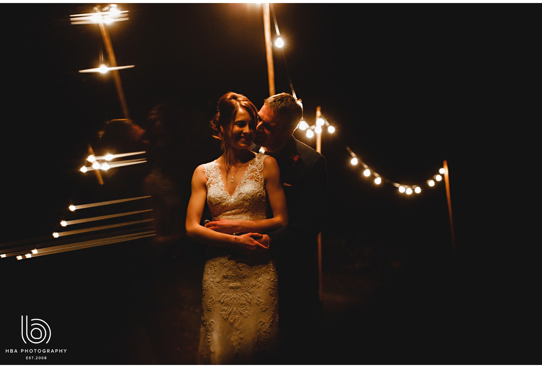The bride and groom in the festoon lighting