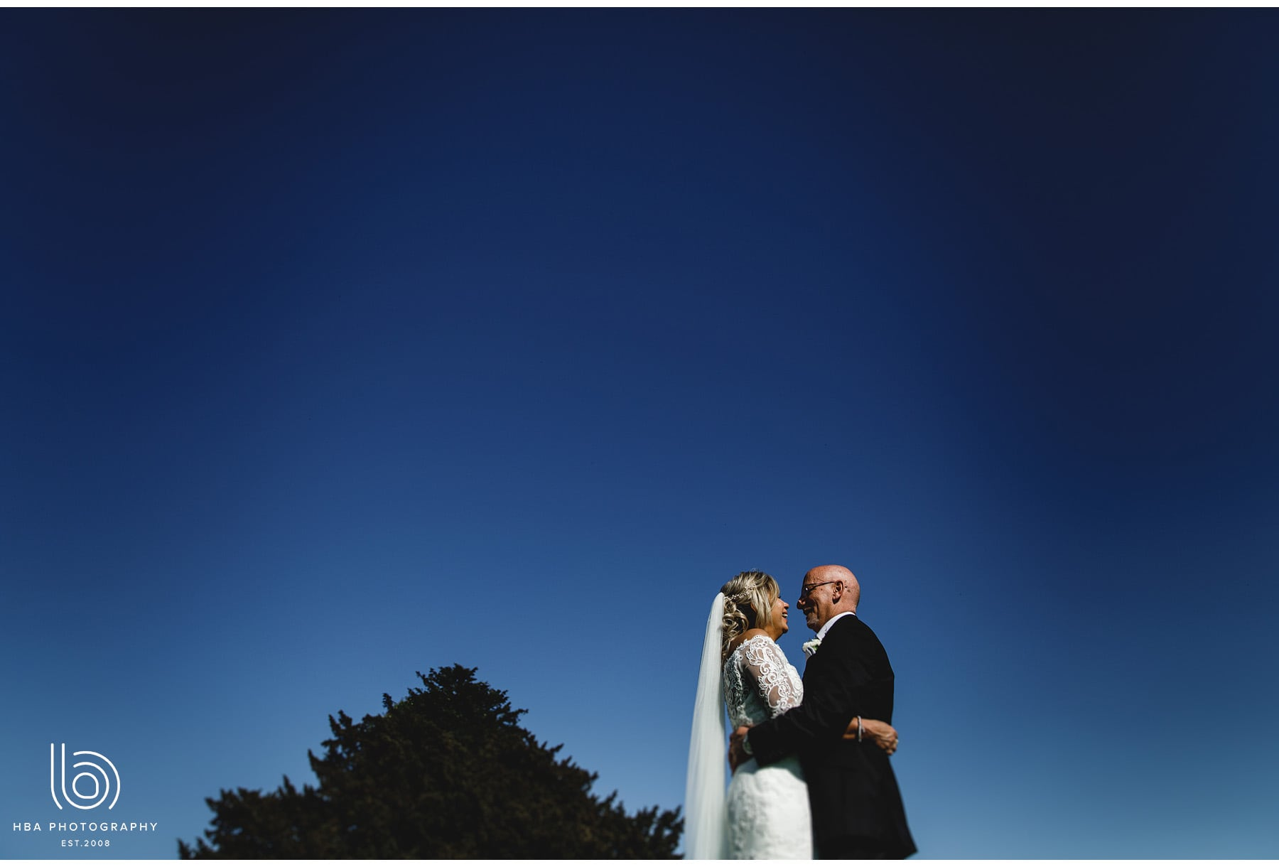 the bride & groom against a bright blue sky