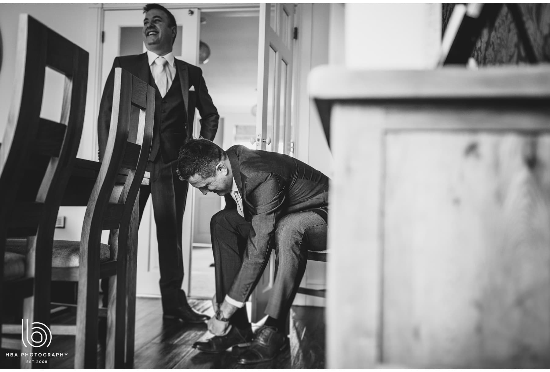 the best man doing up his shoes