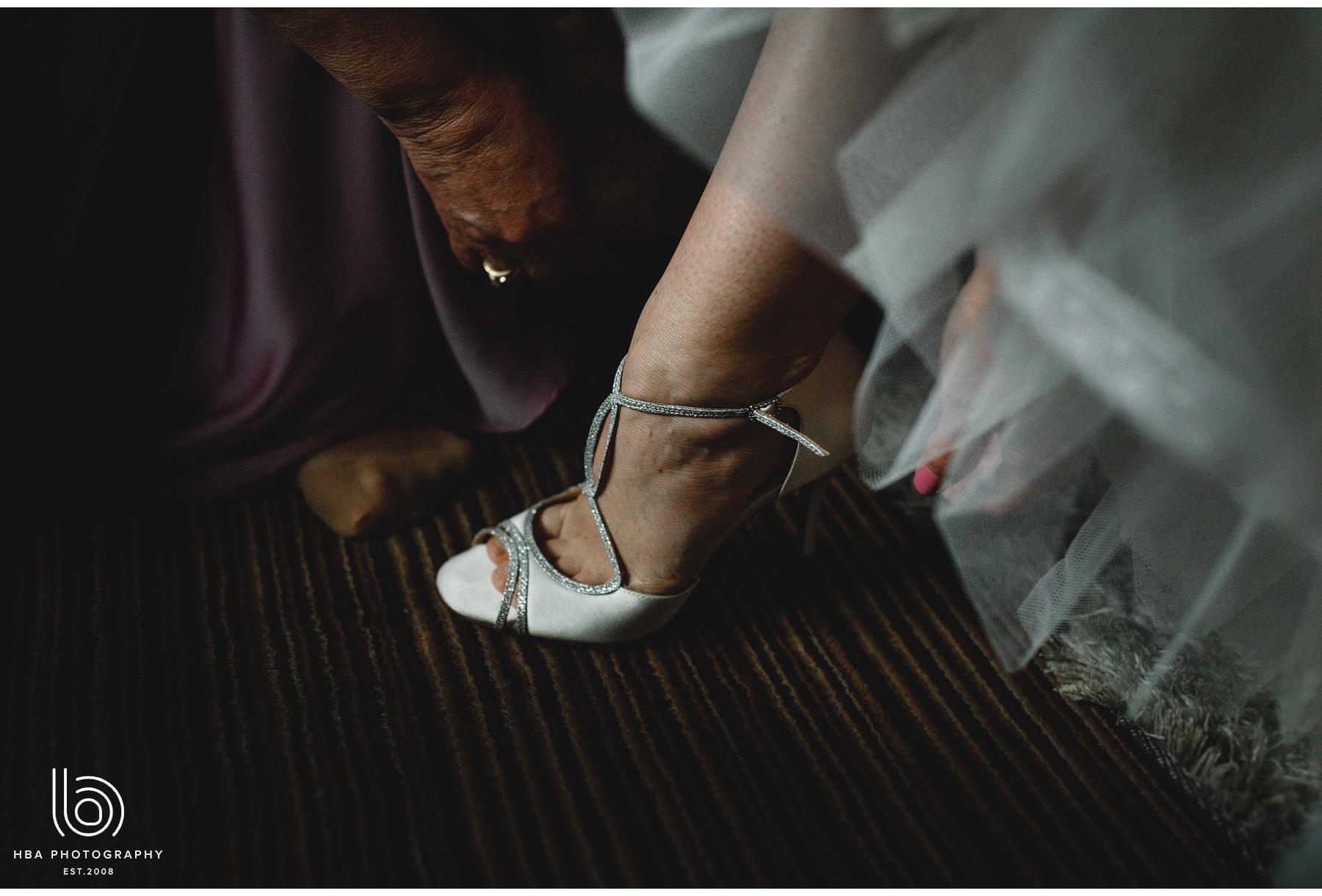 mum putting on brides shoes