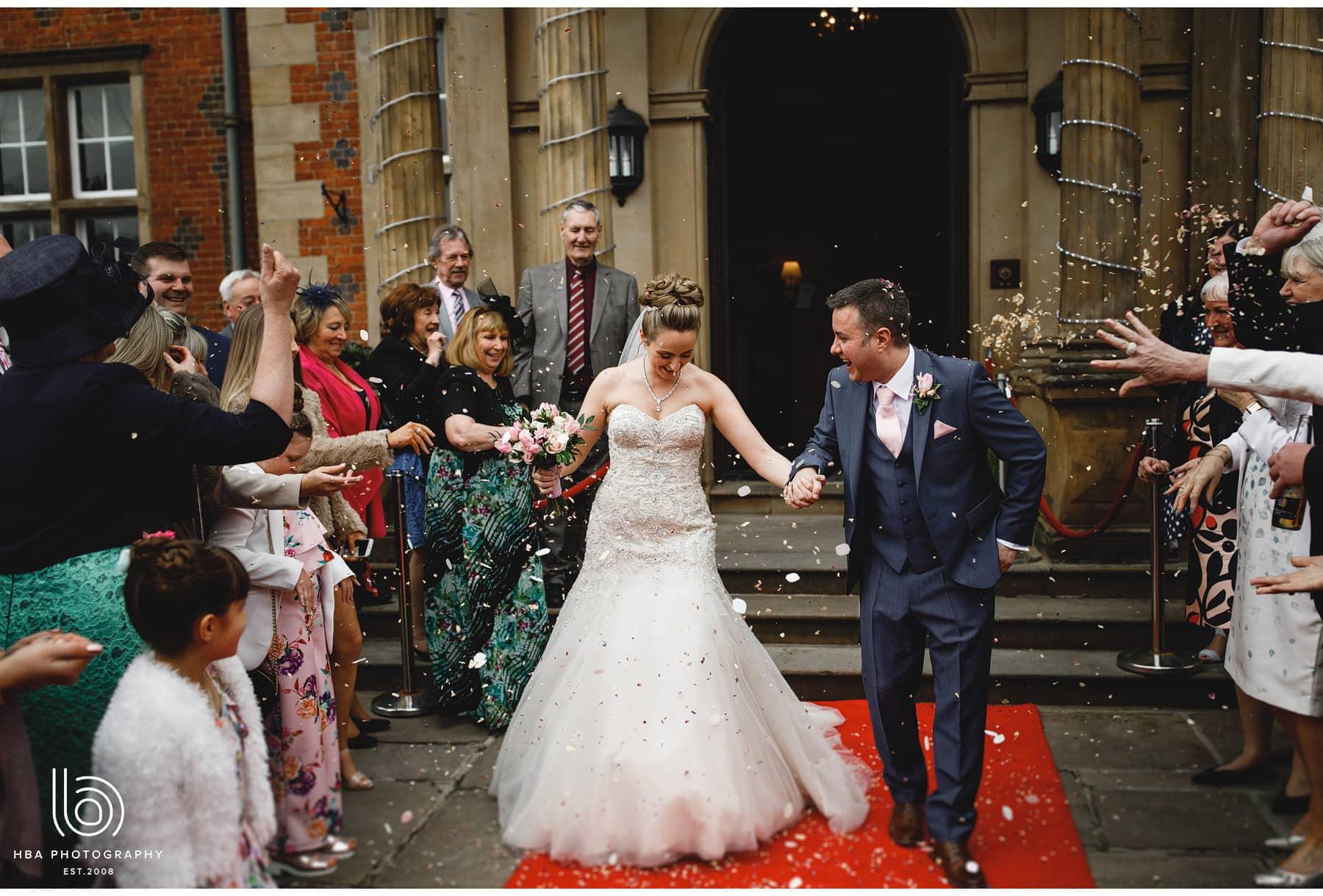 the bride & groom with confetti