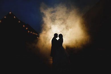 the bride and groom stood in dark orange smoke at the Ashes