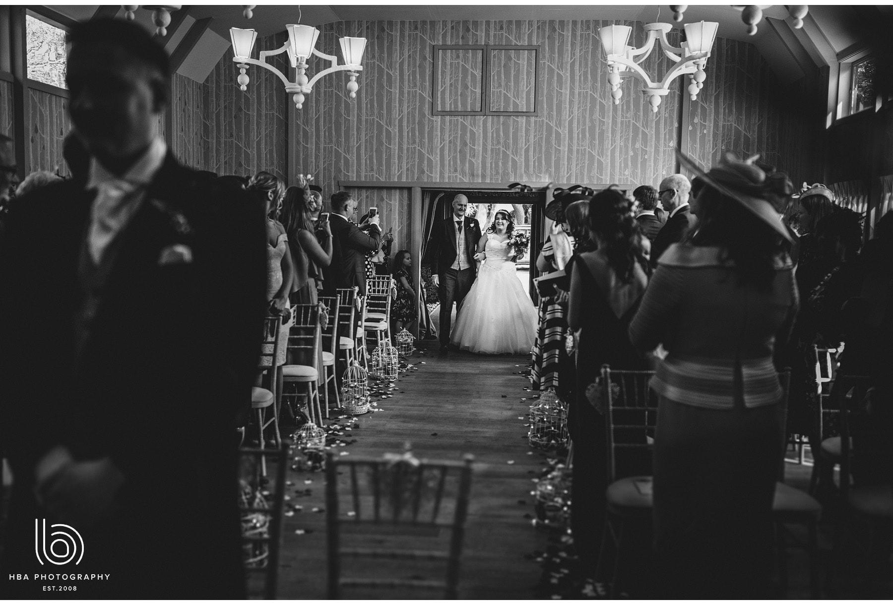 bride and dad walking into bride