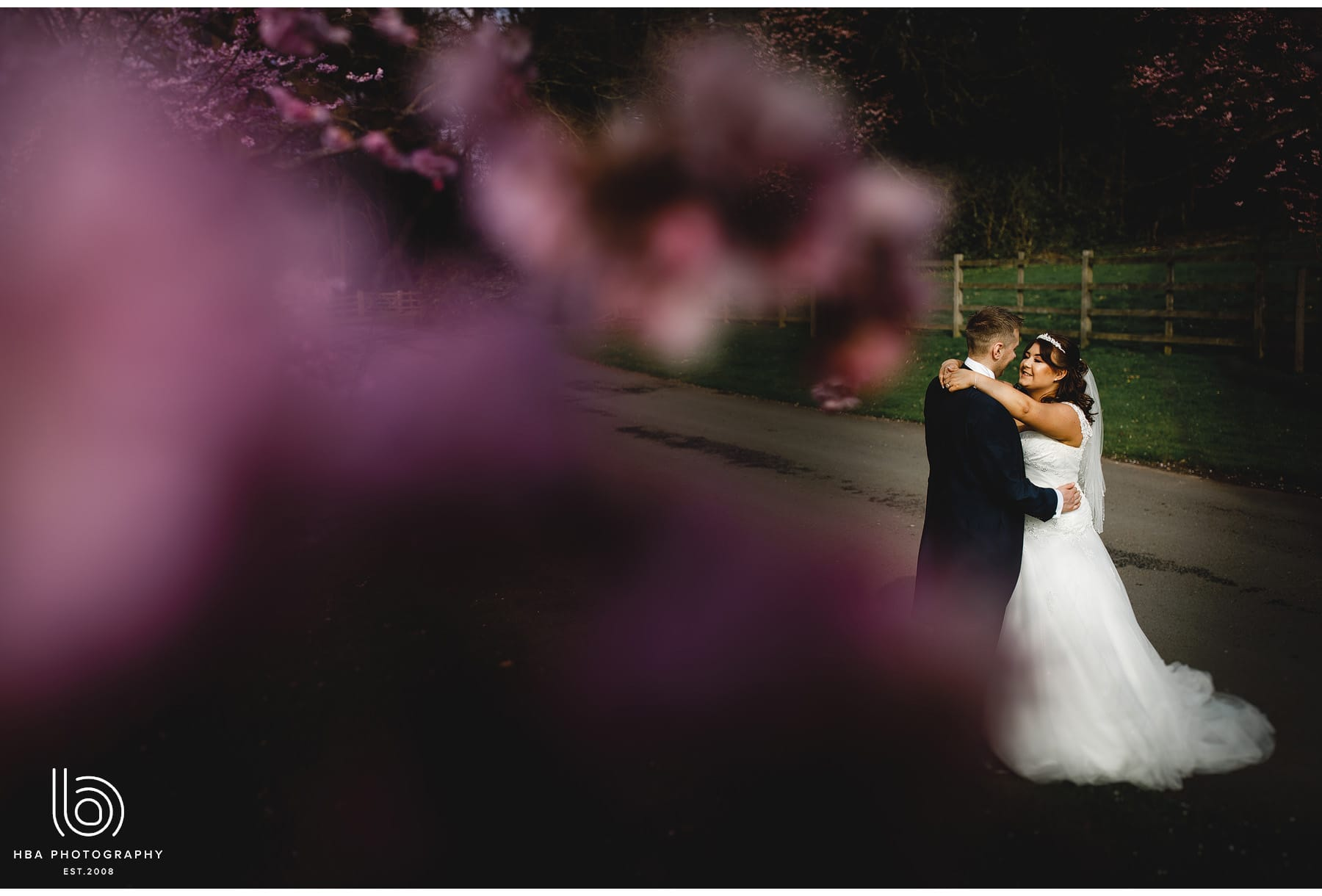the bride & groom through the blossom