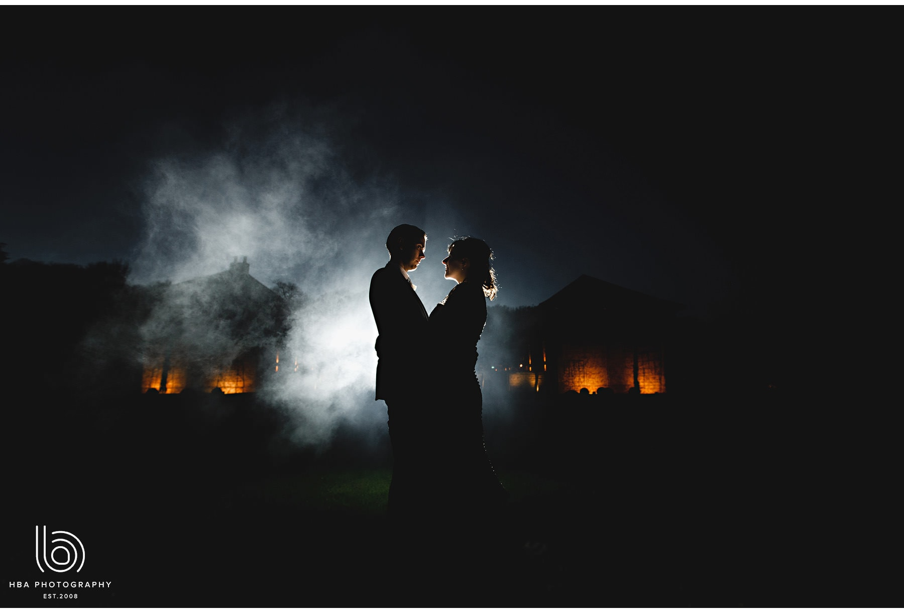 the bride and groom at night in the mist.