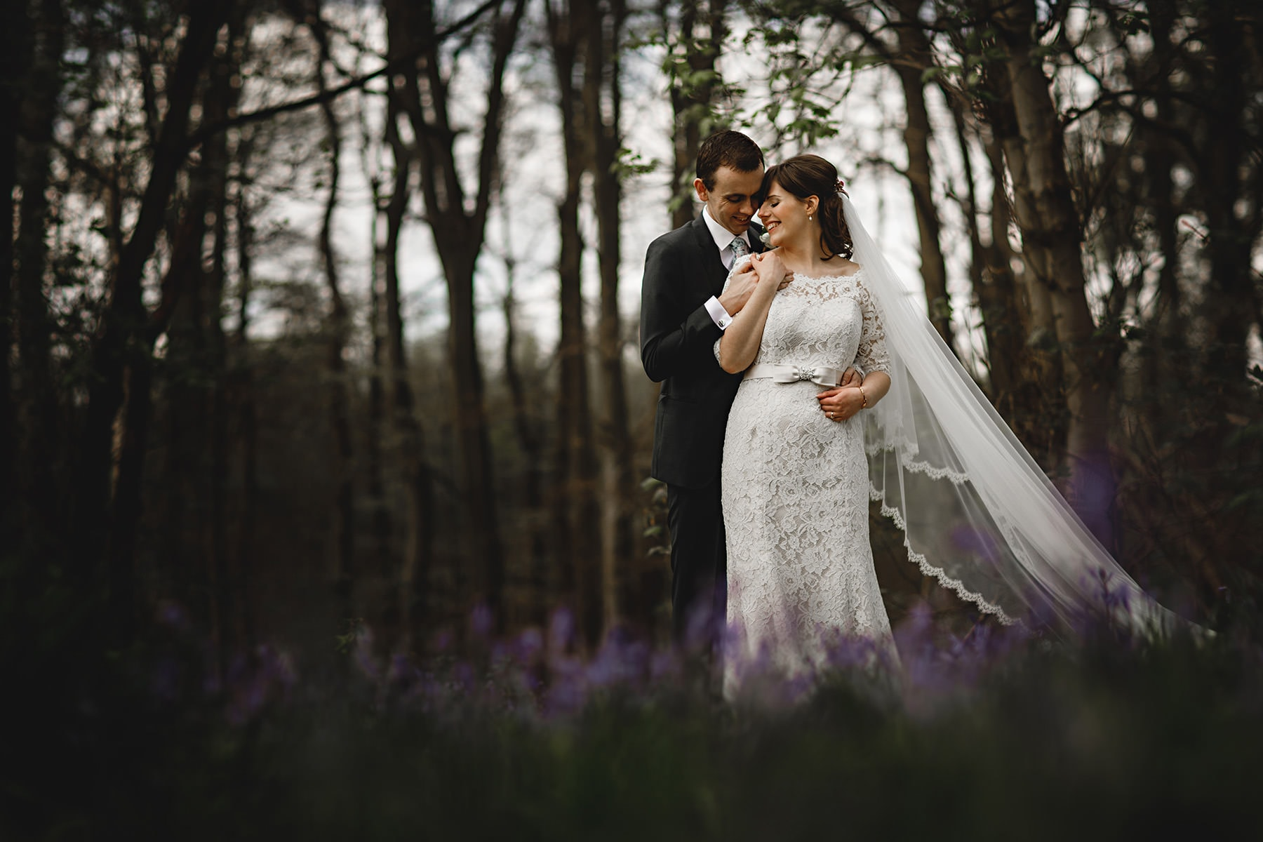 bride and groom stood in the bluebell woods at Hazel Gap on their spring wedding