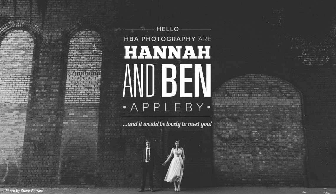 Ben and Hannah stood against a brickwork wall having their photo taken in black and white
