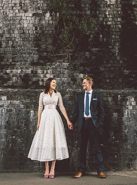 Hannah and Ben, Derbyshire wedding photographers, stood next to each other against a dark brick wall. Ben wearing a blue suit, and Hannah wearing a polkadot dress with pink shoes