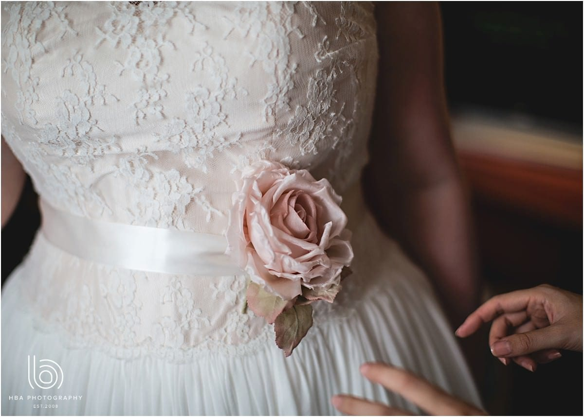 close up photo of a white wedding dress and a pink rose detail