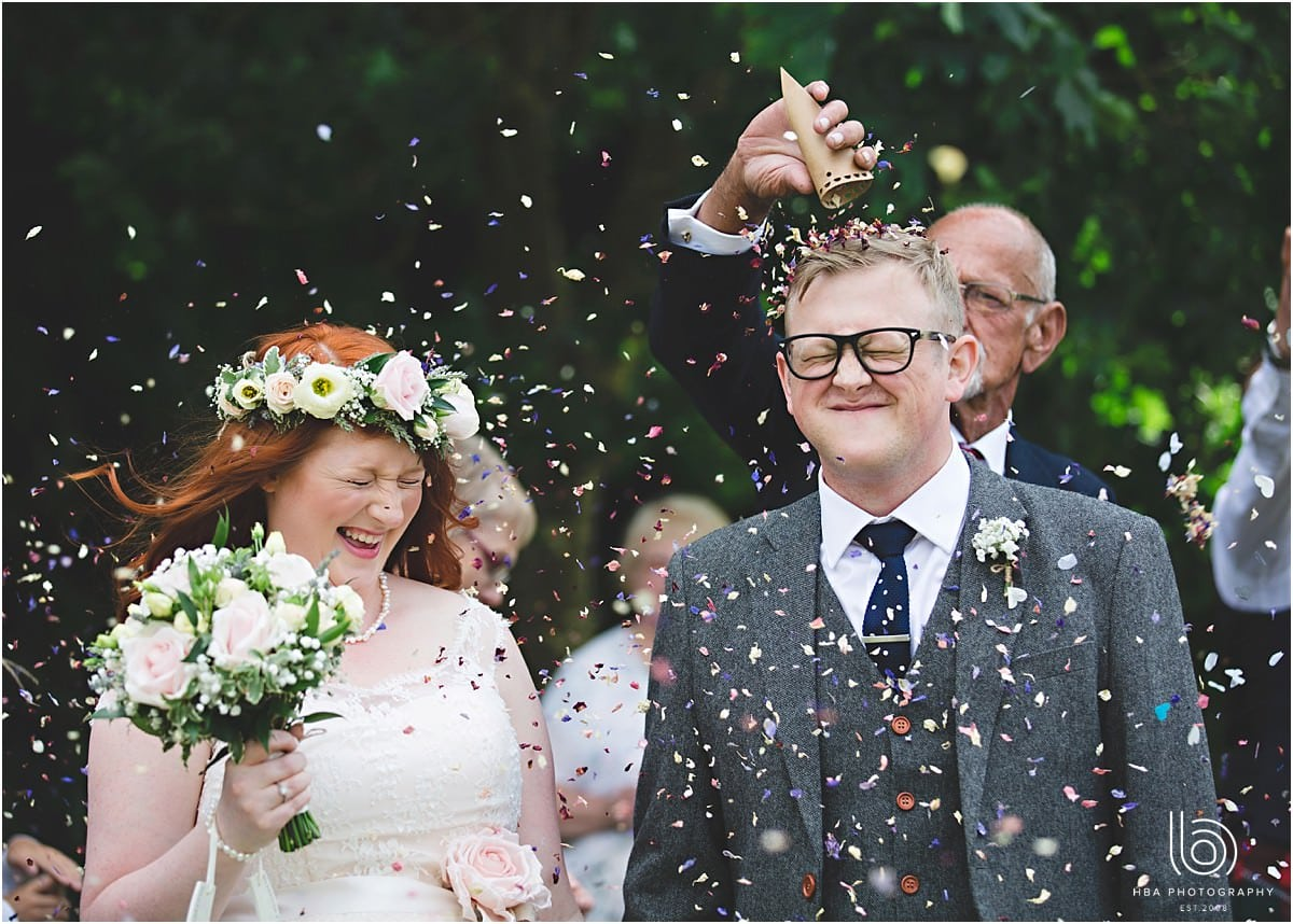 the bride and groom pulling a face as they get covered in confetti