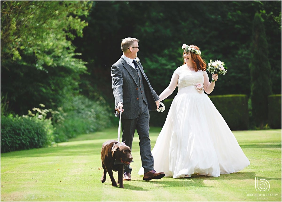the bride and groom walking their dog on the wedding day