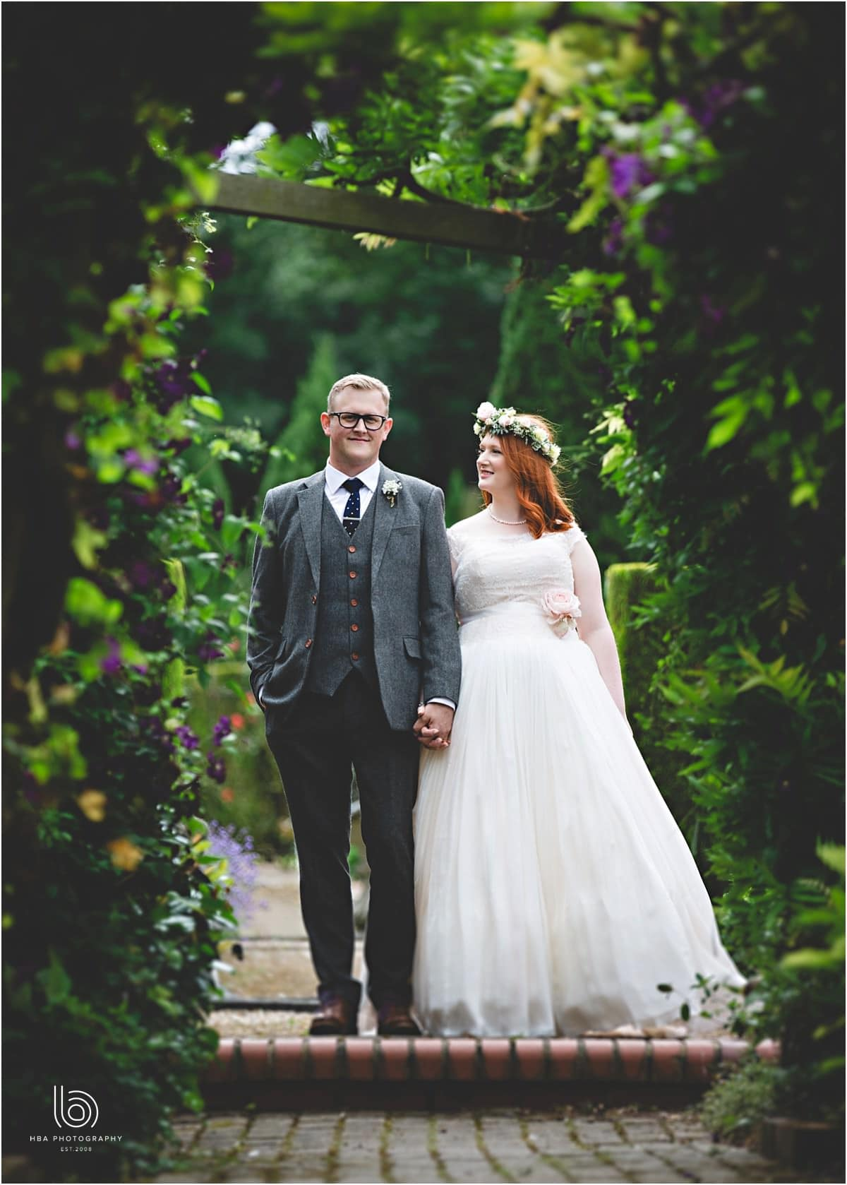 the bride and groom surrounded by green leaves