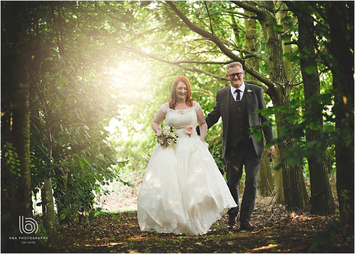 Jamie and Tina walking through the woods in their wedding suit and dress