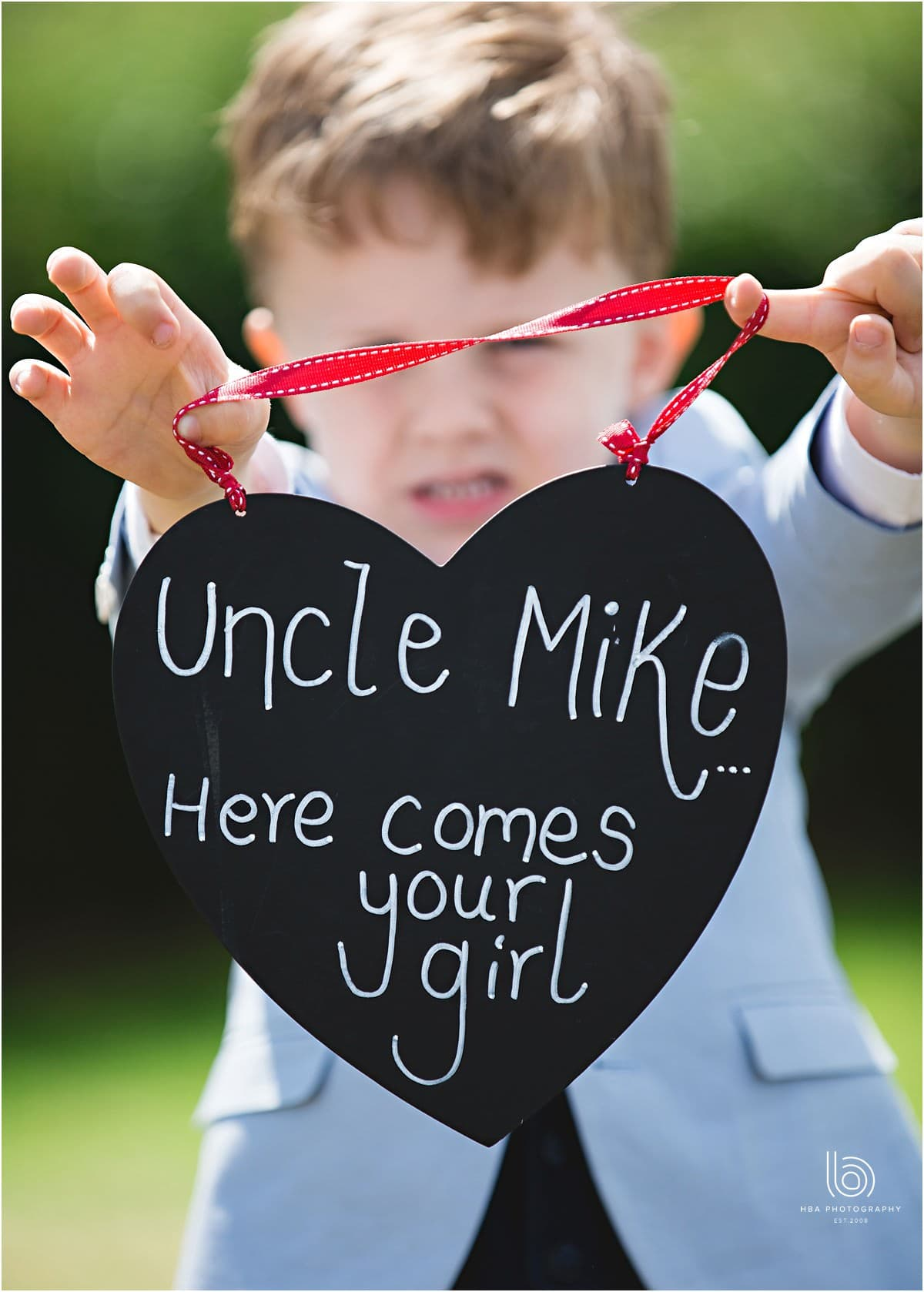 the page boy holding a sign for the ceremony
