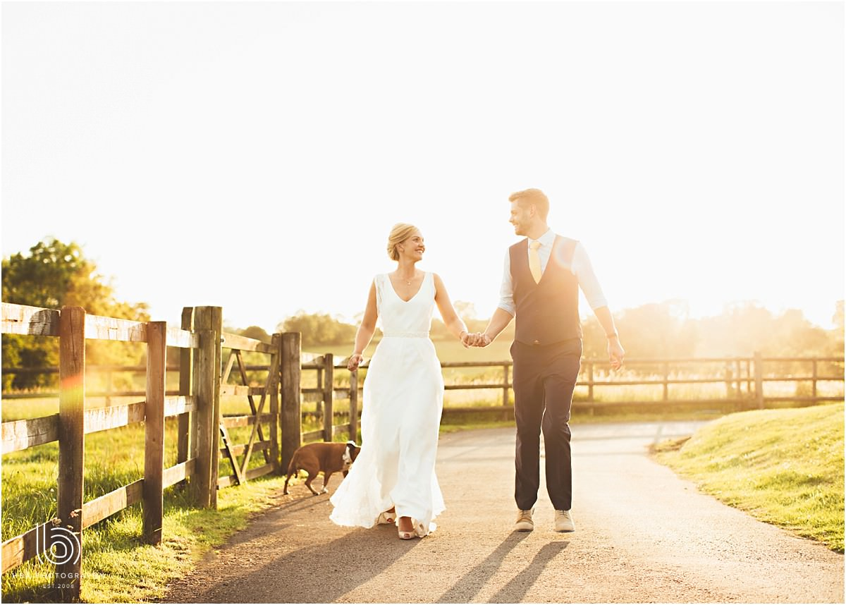 bride and groom running with their dog in the sunshine