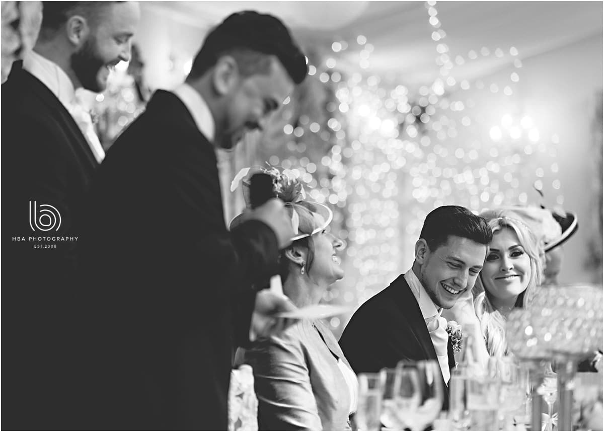 the bride and groom laughing at the best man speech
