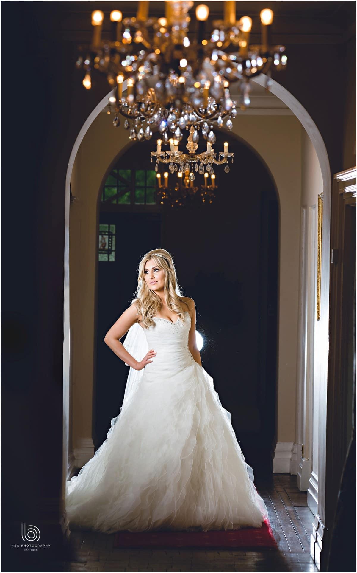 the bride stanifn under a chandeleir at Wrenbury Hall