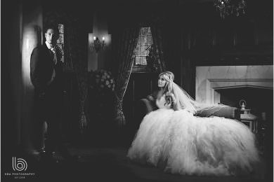 the bride and groom by the fireplace at Wrenbury hall in cheshire