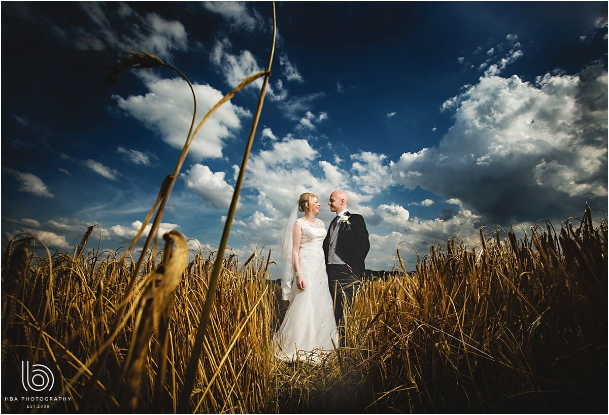 the bride and groom in a corn field with blue sky