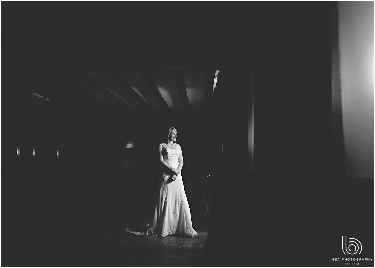 a dramatic black & white image of the bride in a window