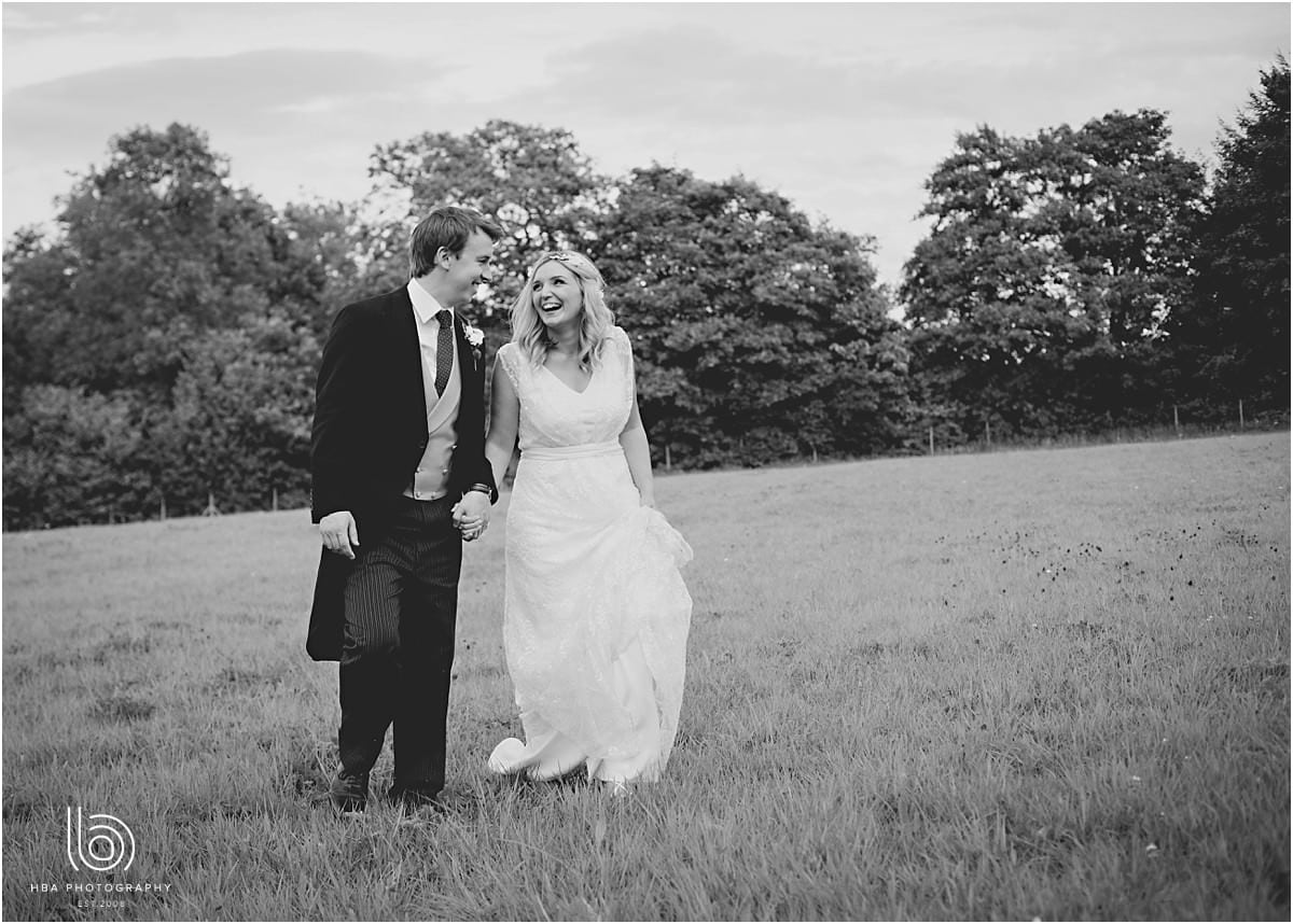 the bride and groom walking in a meadow