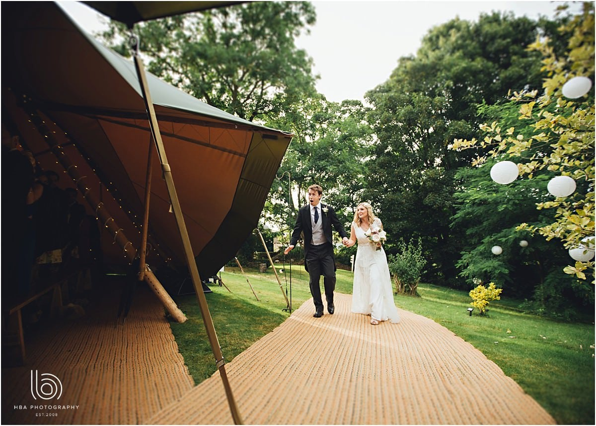 the bride and groom walking into the tipi for the wedding breakfast