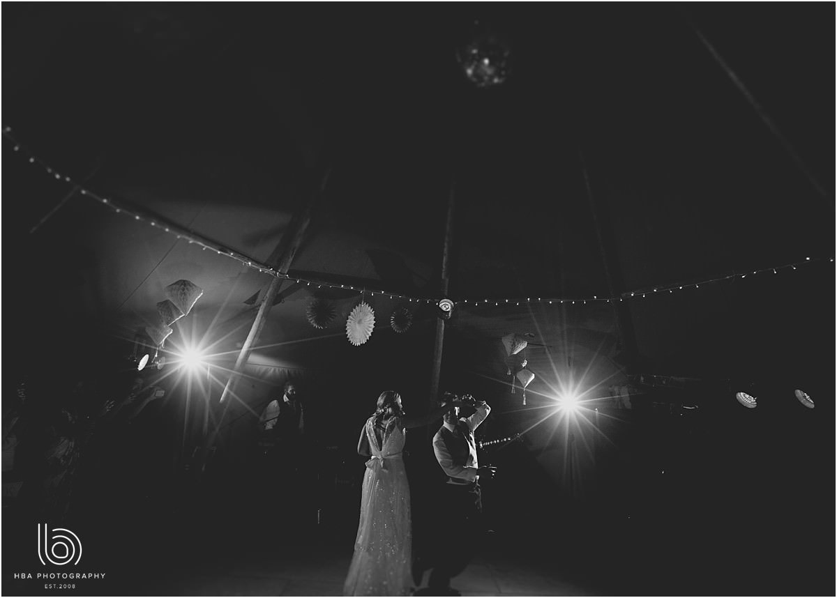 the bride and groom doing their first dance in the tipi