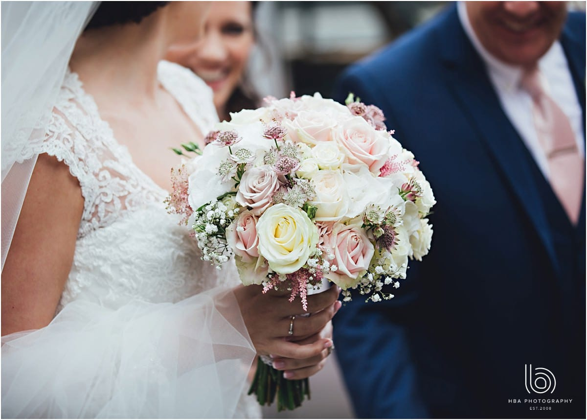 the bride holding a pastel boquet