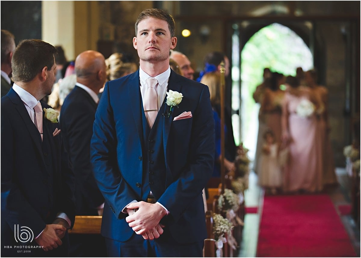 the groom in a blue suit waiting at the front of the isle