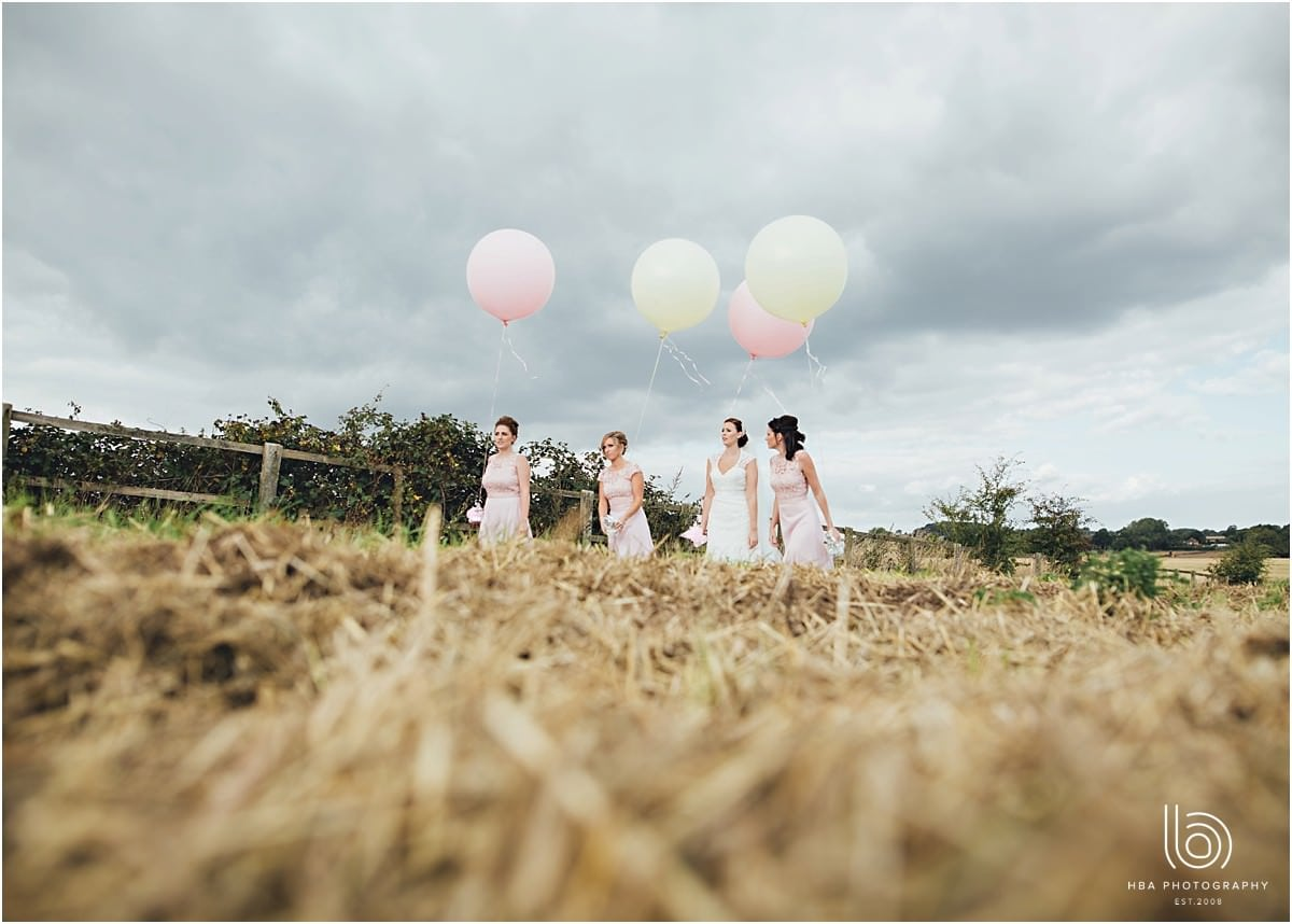 the bride and bridesmaids wearing pink walking holding matching pink and white balloons