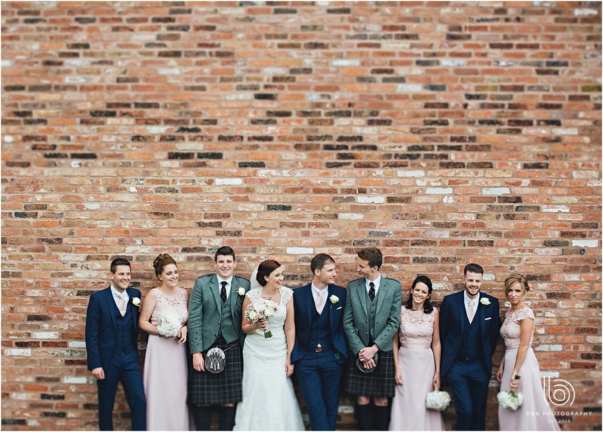 the bridal party stood by a brick wall