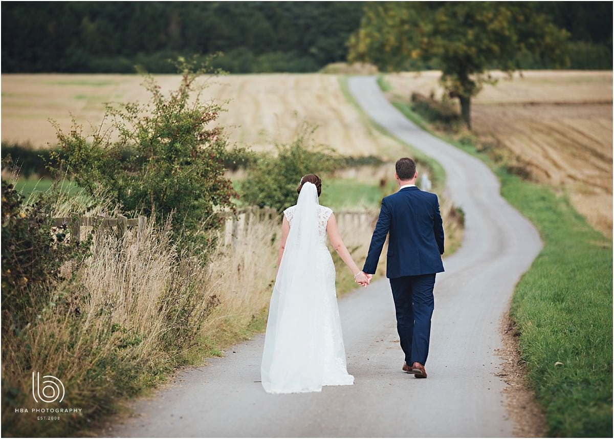 the birde and groom walking down the road