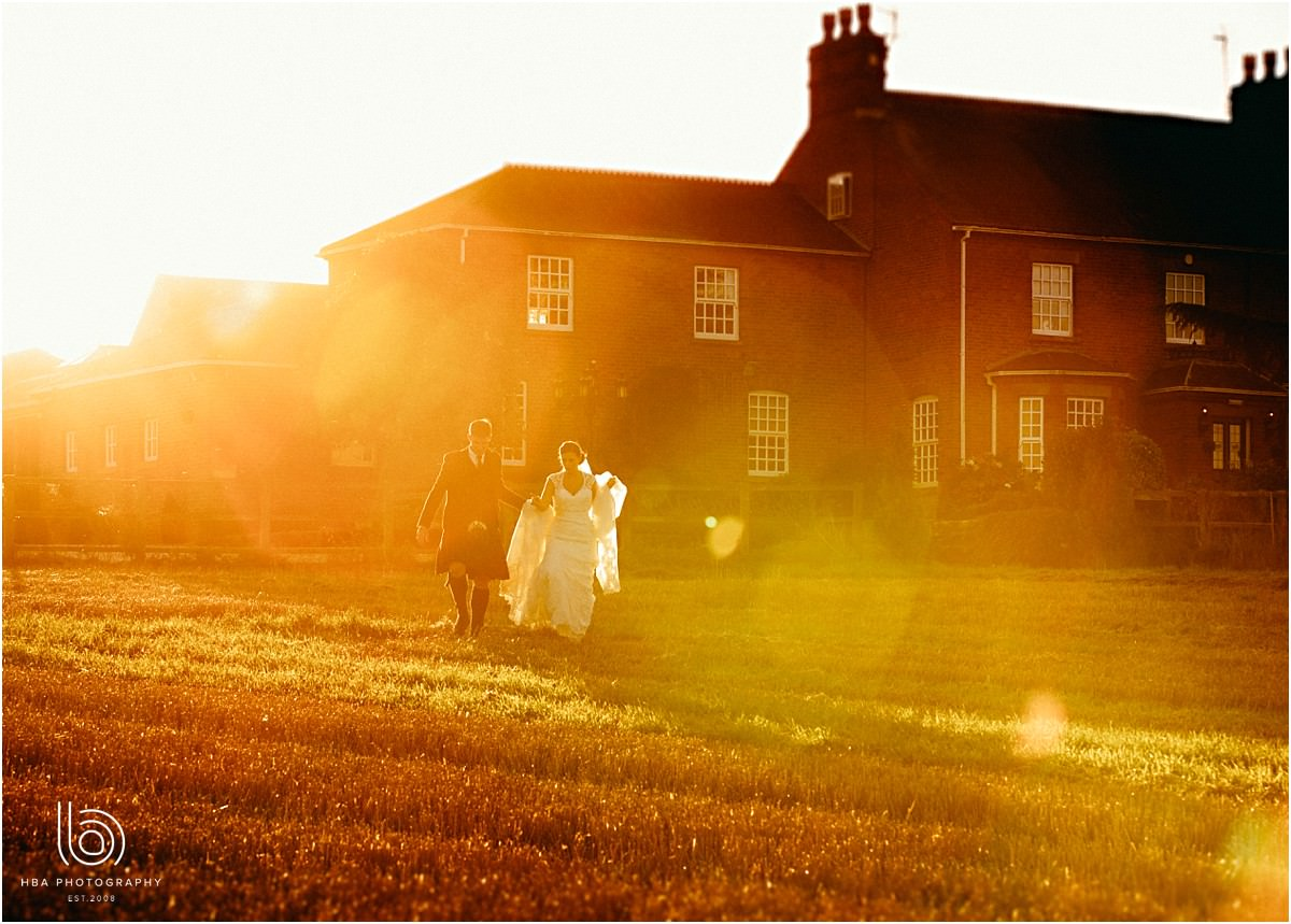 the bride and groom walking into flared sunlight at Swancar